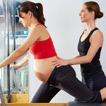 44274510 - pregnant woman pilates reformer cadillac exercise workout with personal trainer